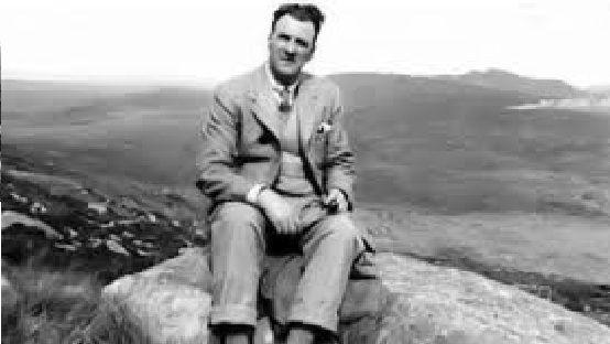 Arthur Kingsley Porter sitting on a rock