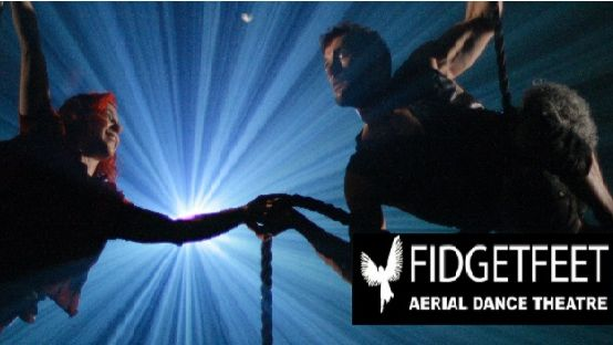 Image of two people swinging in front of a blue light with the fidget feet logo in front