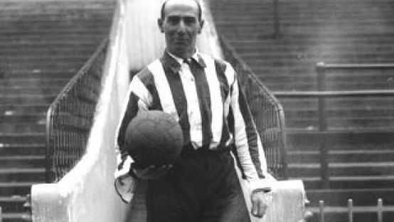 Black and white photo of Billy Gillespie holding a football in front of the match stands