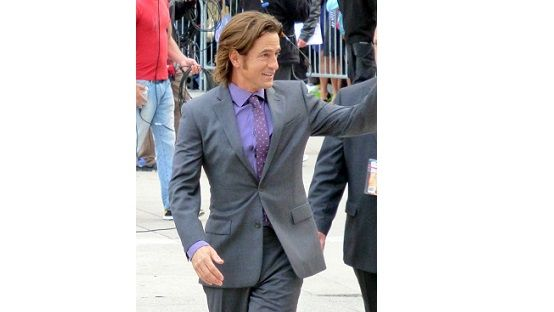 Dermot Mulroney in a grey suit waving at a public event