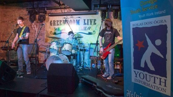 Group of 3 young musicians onstage playing in front of a Greenroom Live banner