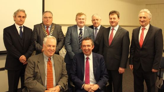 Group of men in suits and ties, two sitting in front, six standing behind
