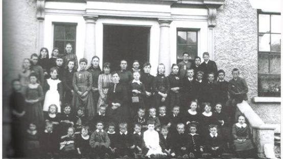 Black and White image of schoolchildren gathered on front steps of house