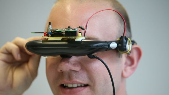 Image of Man looking through technological device on
