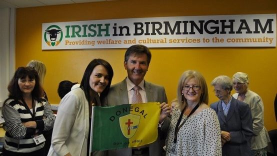 Image of Judy McGroarty, Daniel O'Donnel and Kate Boyle holding a Donegal flag in front of an Irish in Birmingham Banner