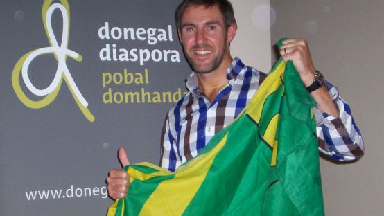 Jason black holding the Donegal flag in front of the Donegal Diaspora Logo