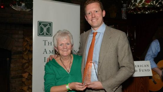 Image of Joe Tully holding his award with his mother beside him