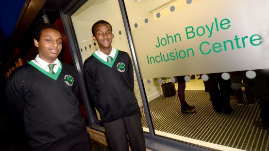 Two school children beside john Boyle Inclusion Centre sign