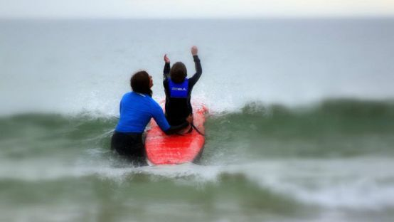 Image of two people in the ocean, one on a surfboard