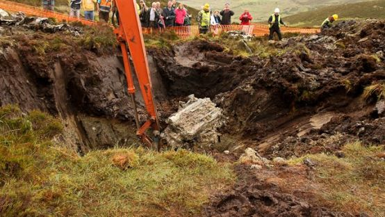 Digger plunging into the bog with people looking on