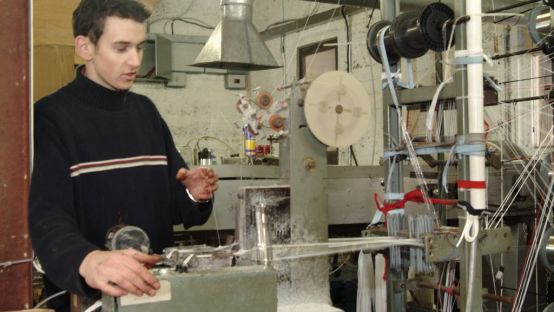 A young man in a black jumper operating machinery