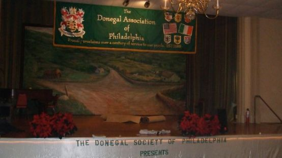 Image of a dimly lit stage with Donegal Association of Philadelphia in the background.
