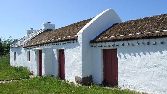 Image of a white thatched cottage with red doors against a blue sky