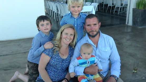 image of blond haired woman, dark haired, bearded man, two young boys and a baby posing for a photo on a hotel step