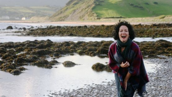 Image of a dark haired woman laughing on a rocky Irish Beach