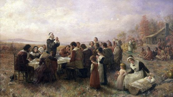 Painting of a number of people, English Pilgrims and Native Americans feasting together. One man is standing with his hands together in prayer