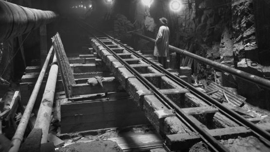 Black and white image of a man in a dimly lit underground train tunnel