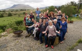 A group singing (pre lockdown) at in the song house garden with the iconic Muckish in the background