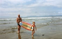 Image of Man and girl carrying a surf-board out of the water