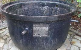 Image of a dark metal famine pot with an incription on the side