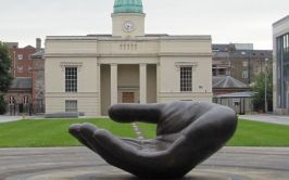 Image of huge hand sculpture in front of a building