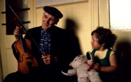 Image of John Doherty holding a fiddle with a young girl beside him.
