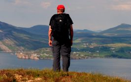 Image of back of man on a hill looking out to sea