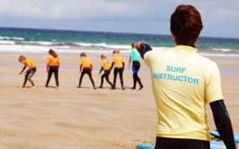 Surfing coach instructing student on the beach