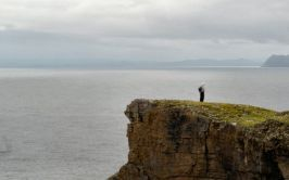 Image of man standing on a cliff edge