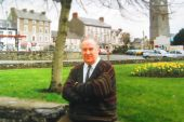 Paddy Harte sitting arms folded by a green area in a town